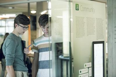 Twee jongeren bekijken de console Communit van de tentoonstelling Conn3ct