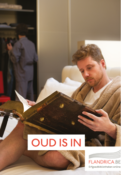 Man reading a large old book in bed
