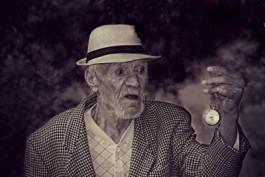 Oude man in de ban van zijn horloge