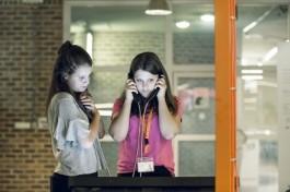 Twee meisjes luisteren naar een van de consoles van de tentoonstelling Conn3ct