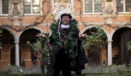 Een man met een kerstkrans in de tuin van het Museum Plantin-Moretus
