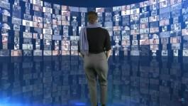 Vrouw kijkt naar groot scherm dat allerlei digitale erfgoedstukken laat zien