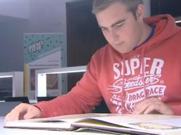 Man lees boek met op achtergrond de Boekensteun-bannier