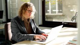 Een foto van Mike Kestemont die werkt op een laptop
