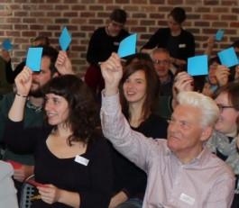Mensen houden blauwe memoblaadjes omhoog