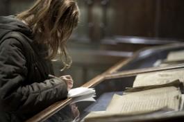 Vrouw maakt aantekeningen bij oud boek in vitrine in Museum Plantin-Moretus