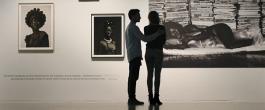 Beeld uit de campagnespot: twee personen staan bij een foto aan de wand
