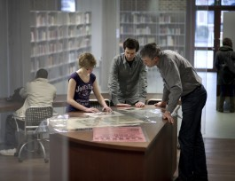3 personen gebogen over beelddocumenten uit de Collectie Limburgensia (BHL)