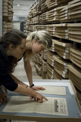 Jonge onderzoekers bekijken een historische krant