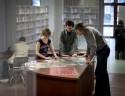 Drie mensen die bibliothecair erfgoed bestuderen