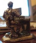 Beeldje van een man aan een bureau met een computer