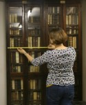 Vrouw meet boekenplank met meetlint