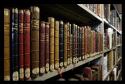 een rij boeken met oude boekbanden op een rek in de kast