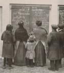 Vrouwen en kinderen kijken naar met krijt op panelen geschreven berichten