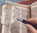 foto van iemand die met een vergrootglas naar een manuscript kijkt