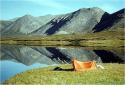 Foto van een tentje nabij een meer in een berglandschap