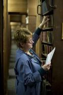 Erfgoedbibliotheekmedewerker aan het werk in het magazijn