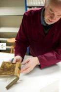 Man aan het werk in het conserveringsatelier van de Openbare Bibliotheek Brugge