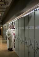 Pater bij compacusrekken in bibliotheekmagazijn