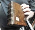 hand met daarin een boek met een oude leren band