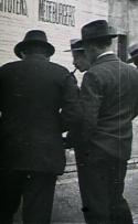 Mannen kijken naar een affiche op de muur