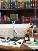Boekenkast met tafel met boekbindersmaterialen ervoor