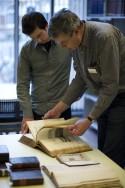 Twee mensen buigen zich over bibliothecair erfgoed