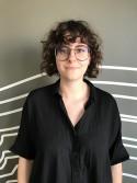 Profielfoto vrouw met bril en kort, donker, krullend haar