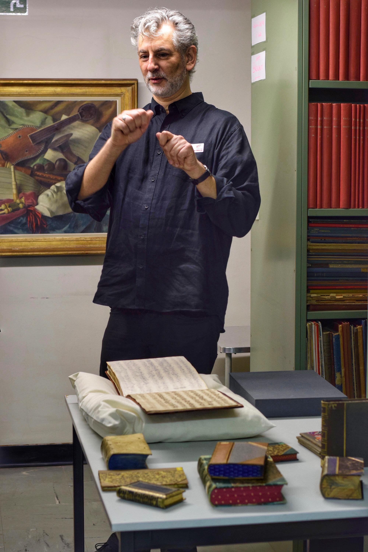 Bibliothecaris toont historische boeken op een tafel